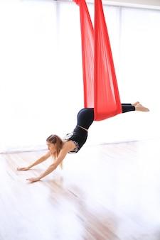 Ginasta feminina treinando sobre o linho vermelho