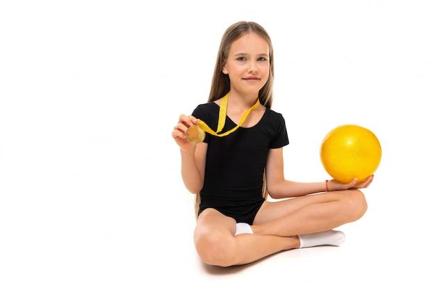 Ginasta garota vencedor, sentada no chão com bola de ginástica em um fundo branco, com espaço de cópia