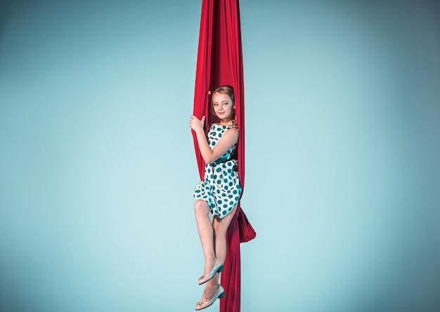 Ginasta graciosa sentada com tecidos vermelhos