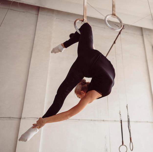 Ginasta loira fazendo um exercício complicado