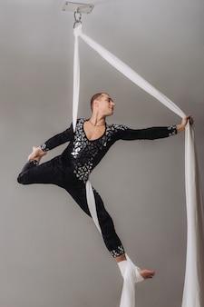 Ginasta masculina fazendo acrobacias de seda aérea