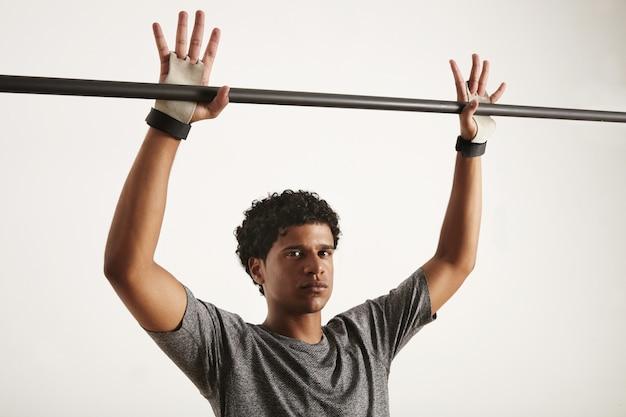 Ginasta negra de aparência séria em camiseta cinza e proteção de ginástica para as mãos se preparando para agarrar uma barra pullup de carbono preto, dedos estendidos, isolado no branco