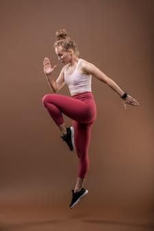 Ginasta ou performer feminina em forma com roupas esportivas, mantendo uma perna dobrada no joelho e dobrando o braço direito no cotovelo enquanto dança