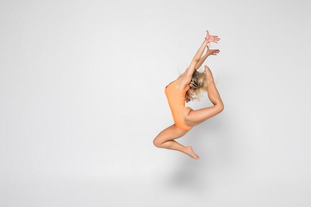 Ginasta sorridente menina flexível em um traje fazendo exercícios de alongamento