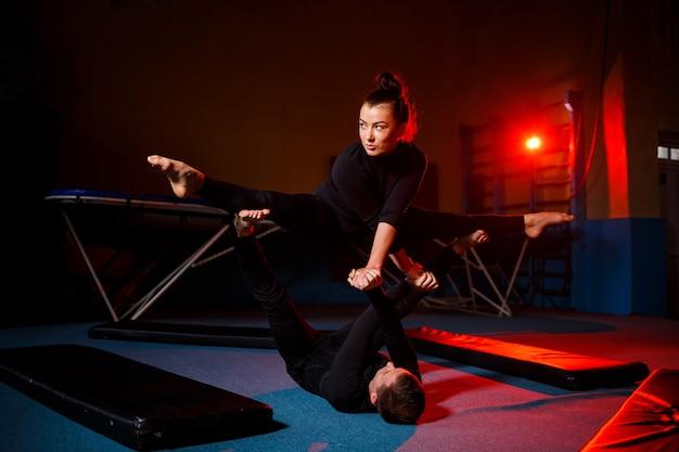Ginastas de jovens e homens fazem exercícios acrobáticos no ginásio. atividades esportivas, estilo de vida saudável