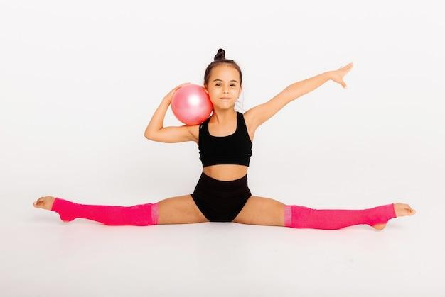 Ginástica artística. menina flexível executa com uma bola em um fundo branco.