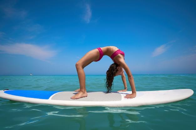 Ginástica de menina na prancha de surf paddle