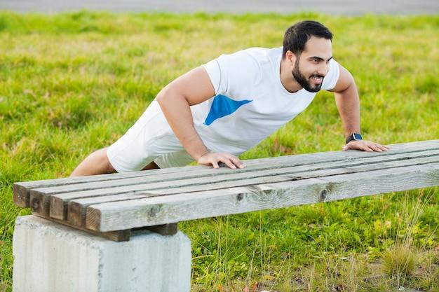 Ginástica. homem de aptidão de exercício de flexão treinando músculos de braços no ginásio ao ar livre.