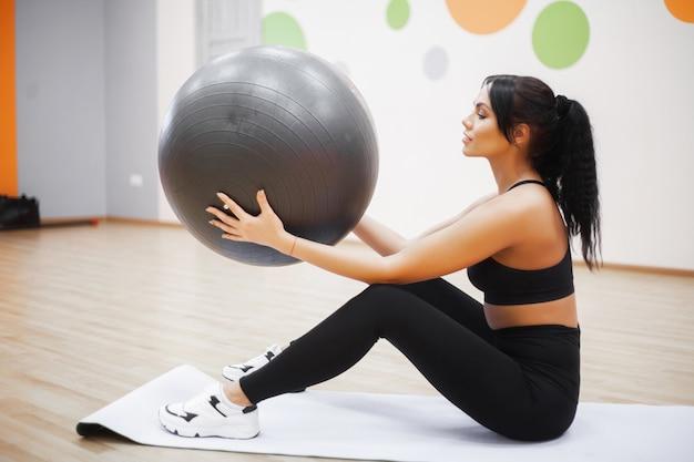 Ginástica. jovem mulher treinando com bola de fitness