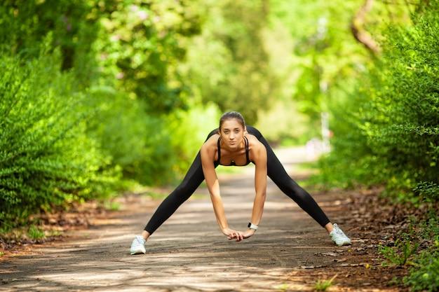 Ginástica. menina do atleta, exercício do thlete fora, aptidão da mulher. jovem mulher bonita, estendendo-se no parque