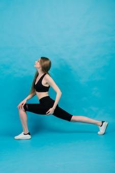 Ginástica. mulher em roupas esportivas, esticando as pernas, aquecendo sobre fundo azul.