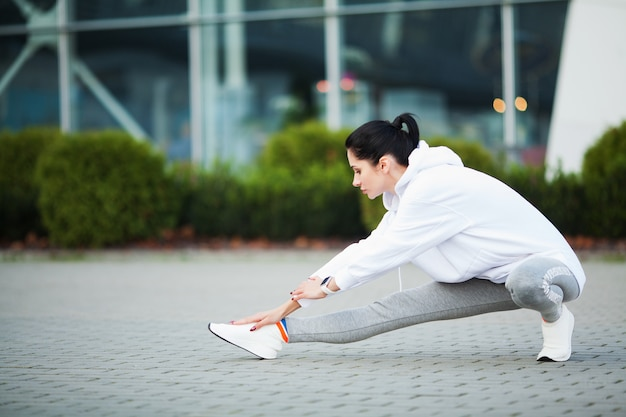 Ginástica. mulher jovem e bonita fazendo exercícios no parque