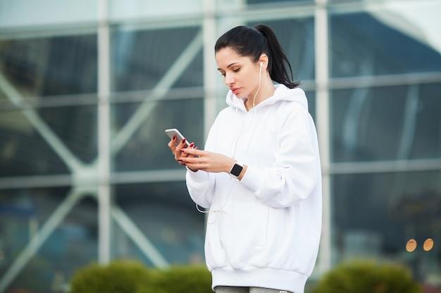 Ginástica. mulher ouvindo música no telefone durante o exercício ao ar livre - esporte e conceito de estilo de vida saudável