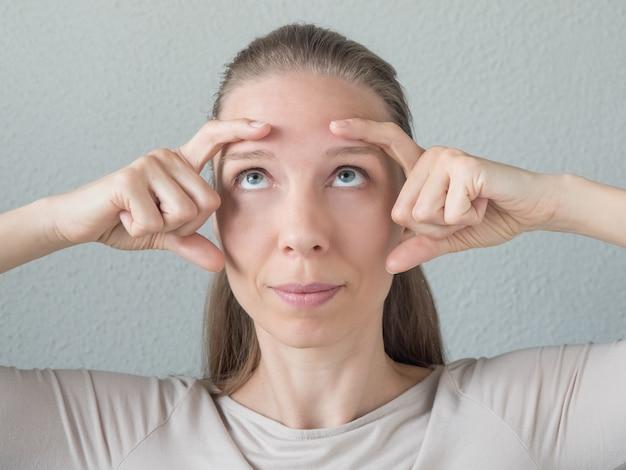 Ginástica para o rosto. mulher faz exercícios rejuvenescedores para o rosto