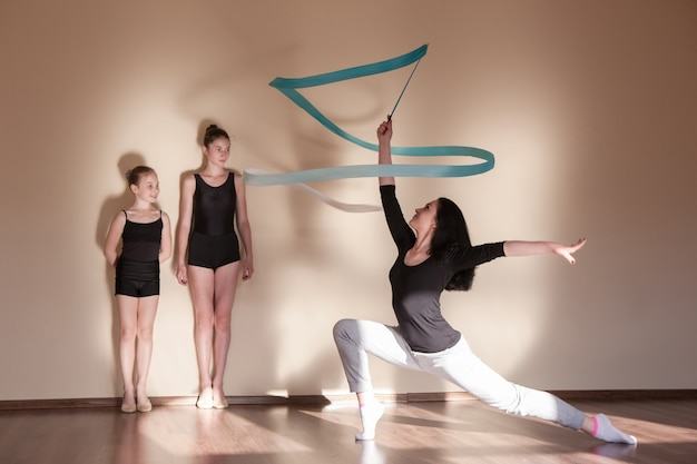 Ginástica rítmica. aula de balé. educação de aulas de bailarinas, esporte adolescente, estilo de vida adolescente saudável. treinadora com meninas, fundo de parede marrom