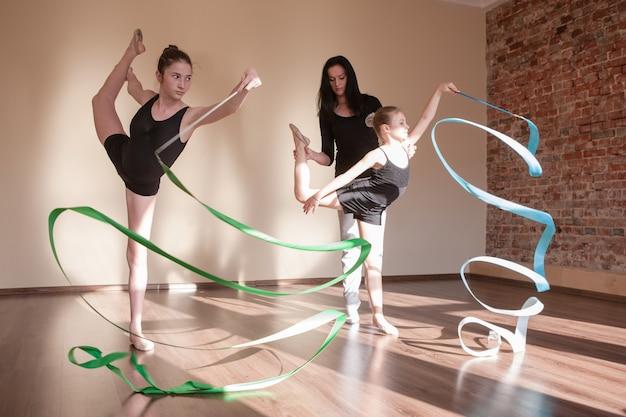 Ginástica rítmica. ensino de aulas de bailarinas. esporte adolescente, estilo de vida adolescente saudável. treinadora com meninas em movimento, plano de fundo da aula de dança, conceito de balé