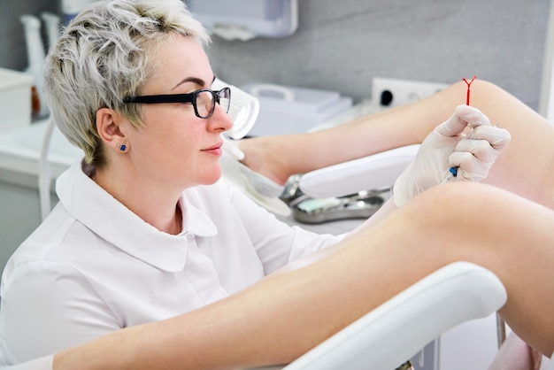 Ginecologista segurando um dispositivo de controle da natalidade do diu antes de usá-lo no paciente