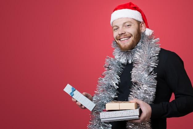 Ginger man com chapéu de papai noel anuncia algo enquanto segura o presente de ano novo na parede vermelha