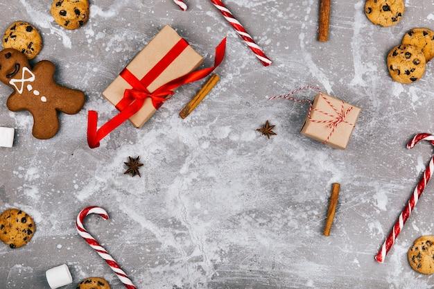Gingerbread, biscoitos, marshmallows, cnadies brancas vermelhas, canela, outras especiarias estão no chão em torno da caixa presente