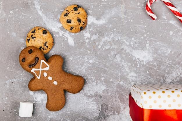 Gingerbread, biscoitos, marshmallows, cnadies vermelhas e brancas estão no chão em torno da caixa presente