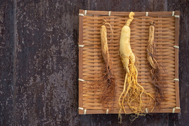 Ginseng fresco e seco no weave de bambu com espaço da cópia no fundo de madeira.