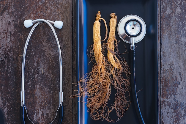 Ginseng seco na placa preta com estetoscópio no fundo madeira