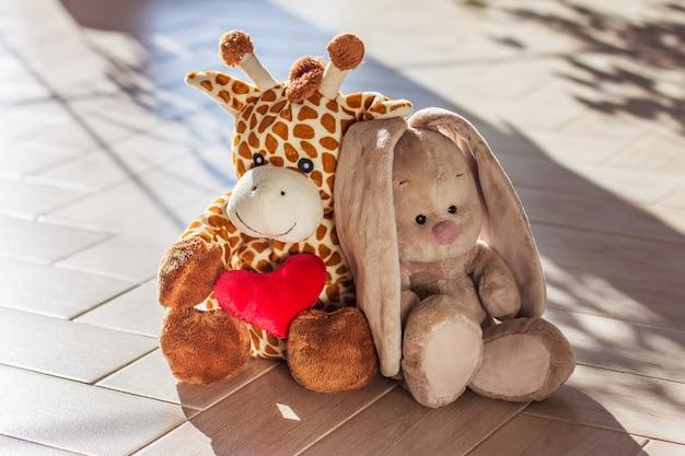 Girafa e coelho de pelúcia macios para crianças sentados em um fundo de madeira, luz forte e sombra