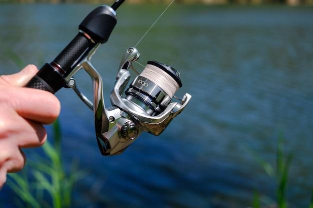 Girando a vara no contexto da ferramenta profissional da lagoa para pescar um peixe predador na linha