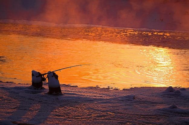 Girando do pescador na margem do rio congelado