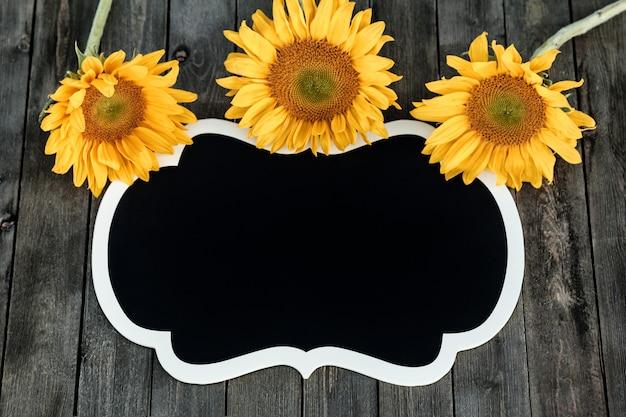 Girassóis amarelos e etiqueta preta em um fundo de madeira