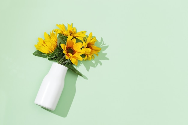 Girassóis amarelos em um vaso branco vista de cima flores desabrochando de outono brilhantes com espaço de cópia