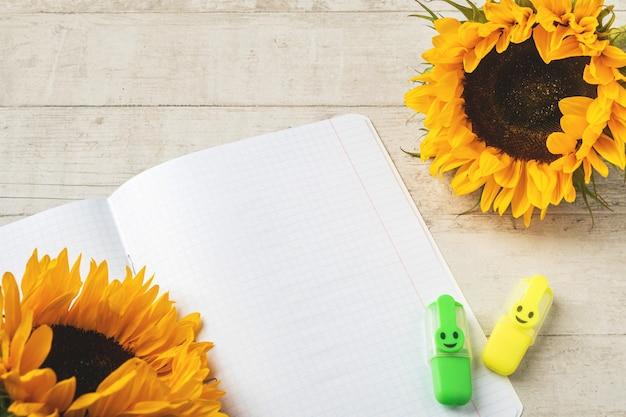 Girassóis, caderno e marcadores