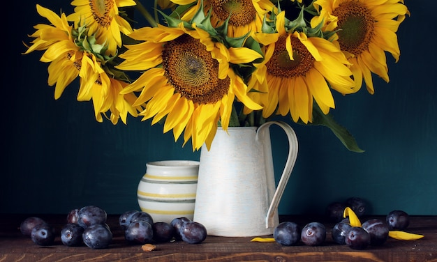 Girassóis e ameixas roxas. flores e frutas. ainda vida com um buquê em um jarro.