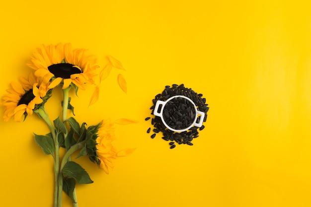 Girassóis e sementes de girassol em uma tigela de cerâmica branca sobre fundo amarelo