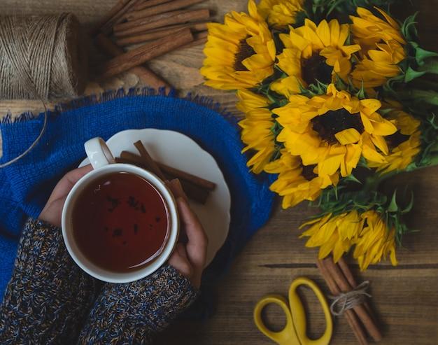 Girassóis e uma xícara de chá quente furada por uma garota