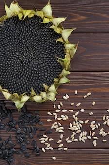 Girassol maduro com sementes descascadas e não descascadas na mesa, vista superior