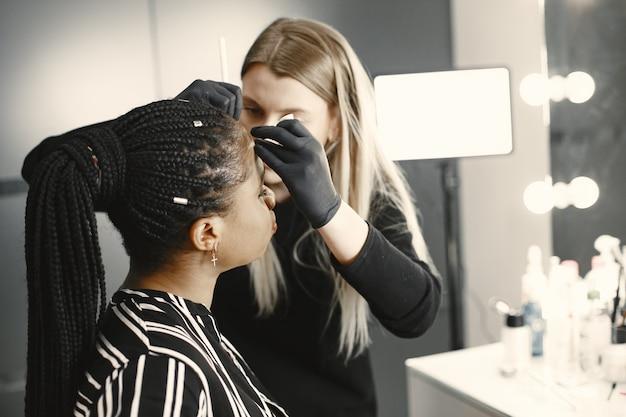 Girl africa. mulher fazendo sobrancelhas. meninas em um salão de beleza.