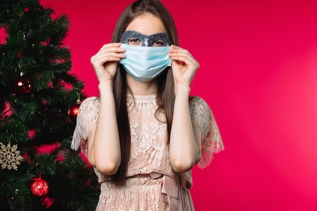 Girrl com carnaval e máscara médica em um fundo vermelho ao lado da árvore de natal