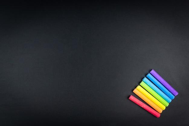 Giz multicolorido no fundo do quadro-negro