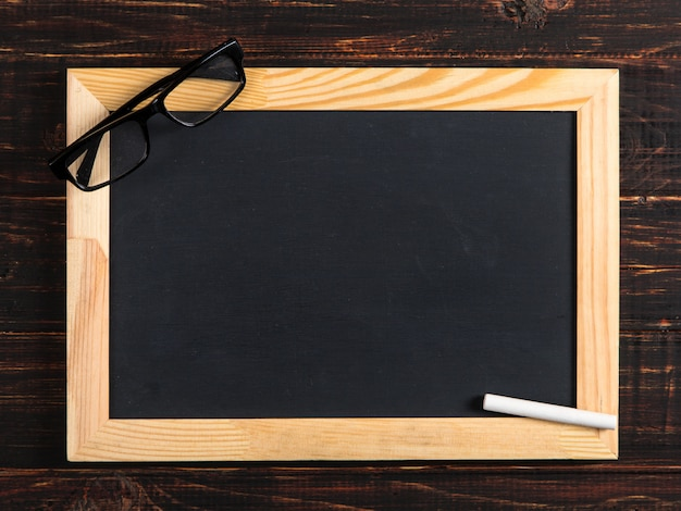 Giz placa preta, óculos e giz em uma mesa de madeira, copie o espaço.