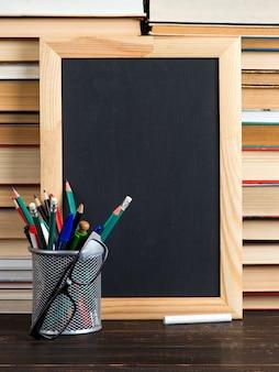 Giz placa preta, óculos, suporte com canetas, lápis e giz, contra livros, copie o espaço.