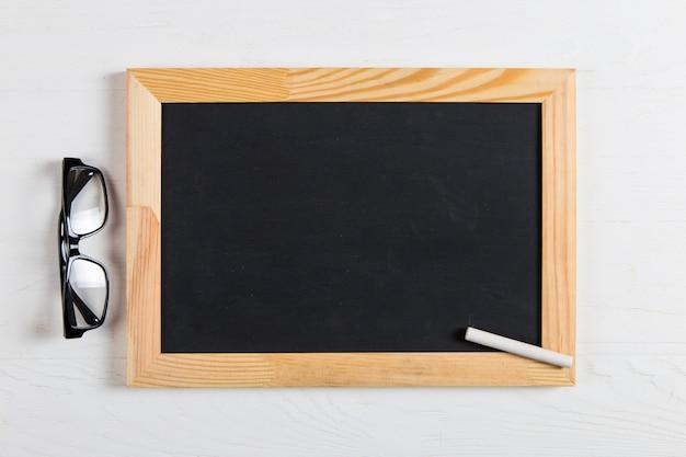 Giz quadro negro, óculos e giz na mesa branca, copie o espaço.