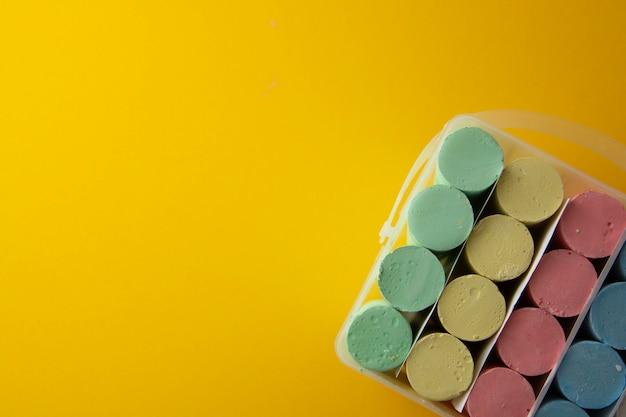 Gizes coloridos sobre o fundo amarelo com espaço da cópia.