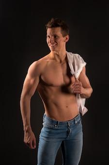 Gladiador ou atlant. esporte e treino. cara com o peito nu em jeans e camisa. homem com corpo musculoso. pose de fisiculturista atlética.