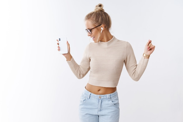 Glamour elegante e mulher caucasiana despreocupada com óculos de suéter cortado, virando-se alegremente acenando com as mãos na dança segurando um smartphone, ouvindo música em fones de ouvido sem fio sobre fundo branco