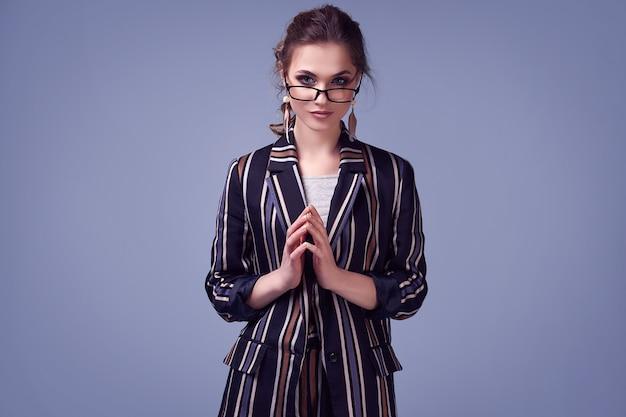 Glamour elegante mulher em traje de moda posando em fundo azul colorido