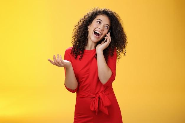 Glamour falante garota boba com cabelo encaracolado se divertindo, sentindo-se despreocupada e feliz contando no celular, virando-se enquanto rindo alegremente, gesticulando com a mão segurando o smartphone pressionado contra a orelha.