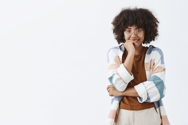 Glamour fofa modelo feminina de pele escura com penteado encaracolado em óculos transparentes e roupa da moda sorrindo amplamente com expressão tímida cobrindo a boca com a palma da mão