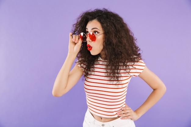 Glamour jovem mulher com cabelos cacheados no desgaste do verão e óculos de sol, olhando de lado