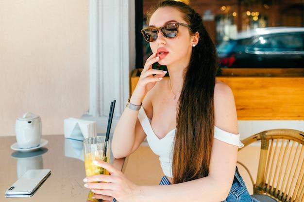 Glamour jovem mulher sexy posando com suco